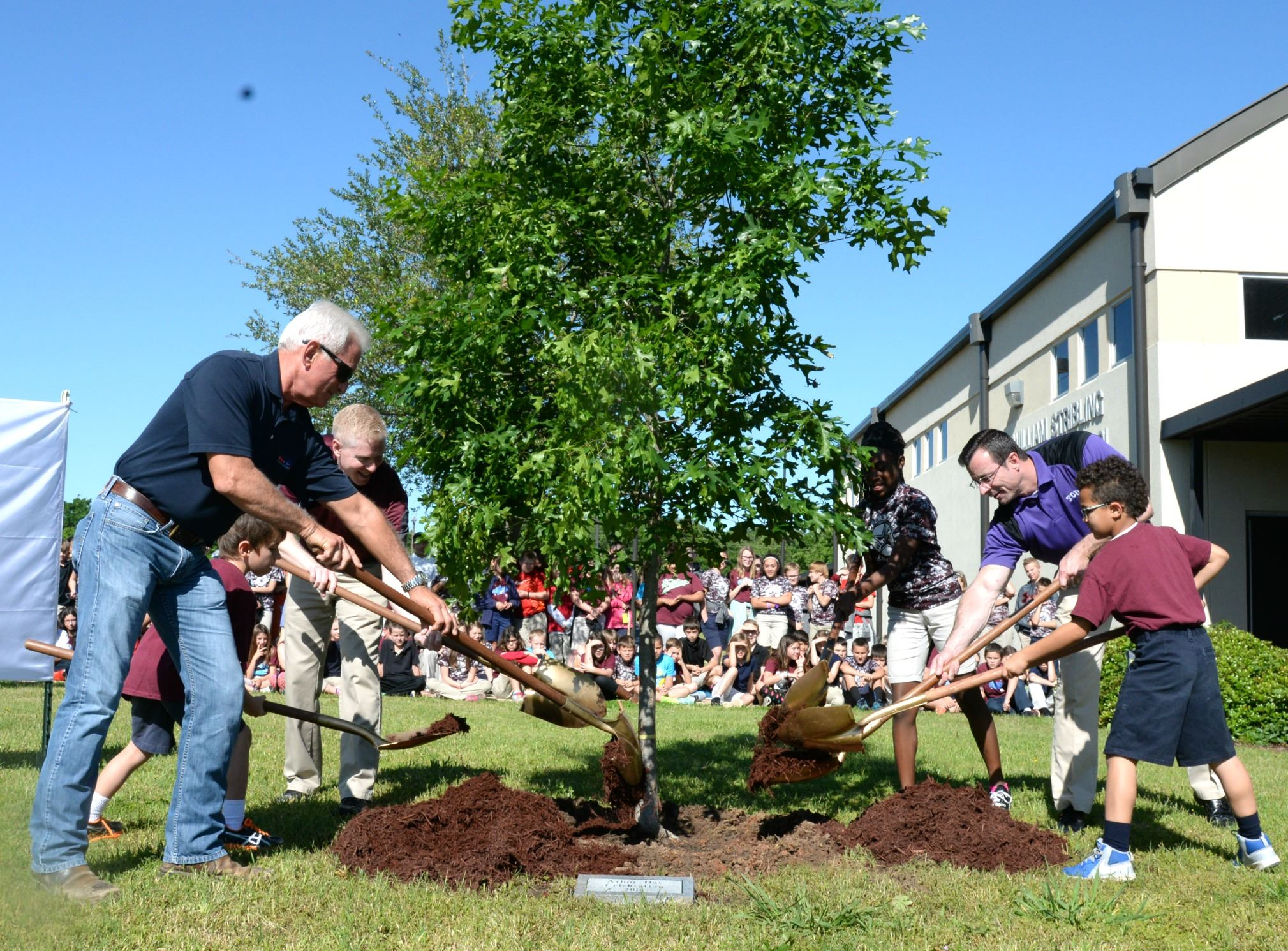 stribling elementary students planting tree at arbor day celebration