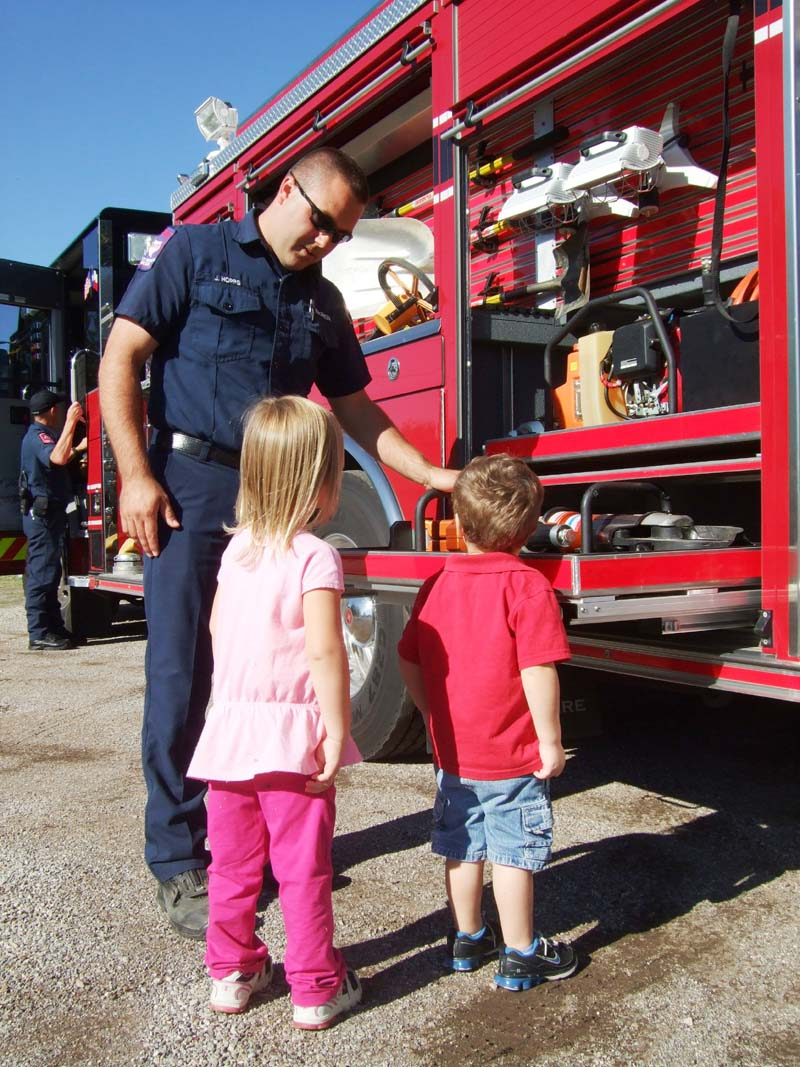 photo of fireman and kids looking at fire truck